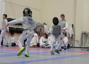Young foil fencers try to find the right fencing strategy in the bout