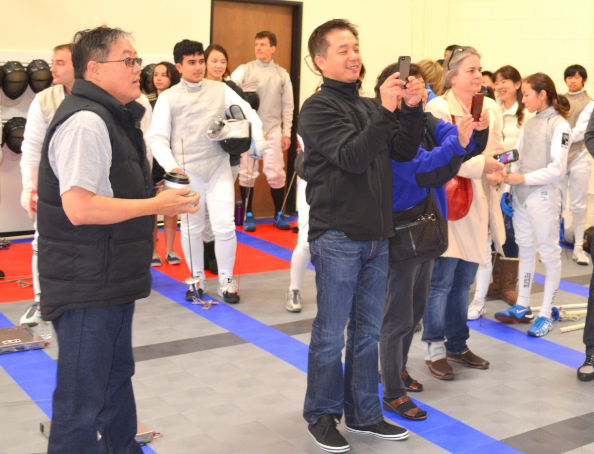 Parents taking pictures on fencing strip during competition